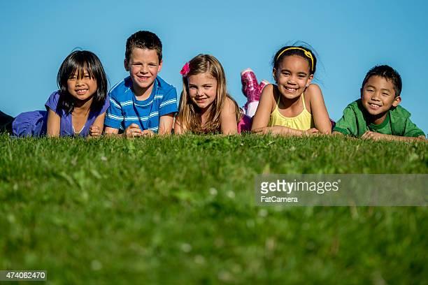 Kinder liegen auf einem Hügel