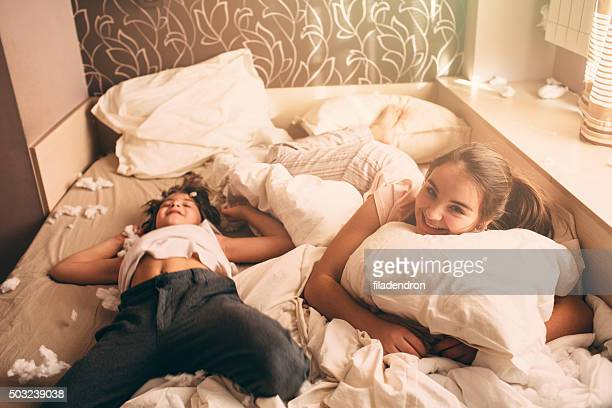 Children lying on bed after fight with pillows