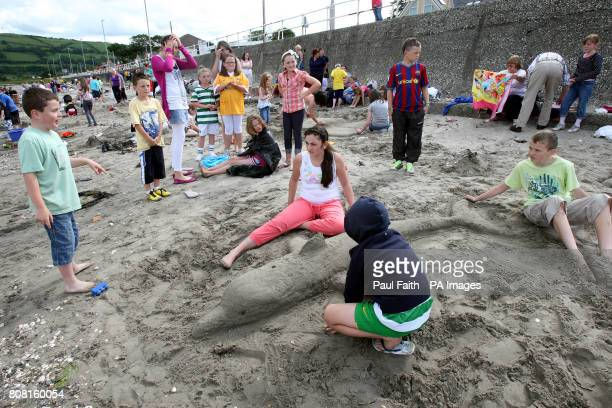 Children make a Dolphin out of sand on Carnlough beach Co Antrim as part of the Village Festival