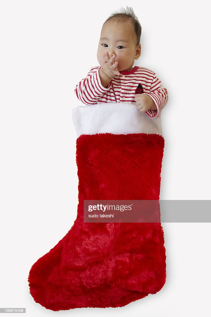 Children make an appearance from Christmas socks. : Stock Photo