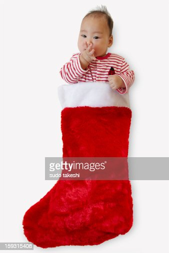 Children make an appearance from Christmas socks. : Stock Photo