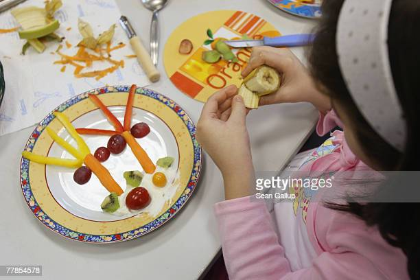 Children make an island scene on their plates out of fruits and vegetables during a class to promote nutrition at an elementary school November 12...