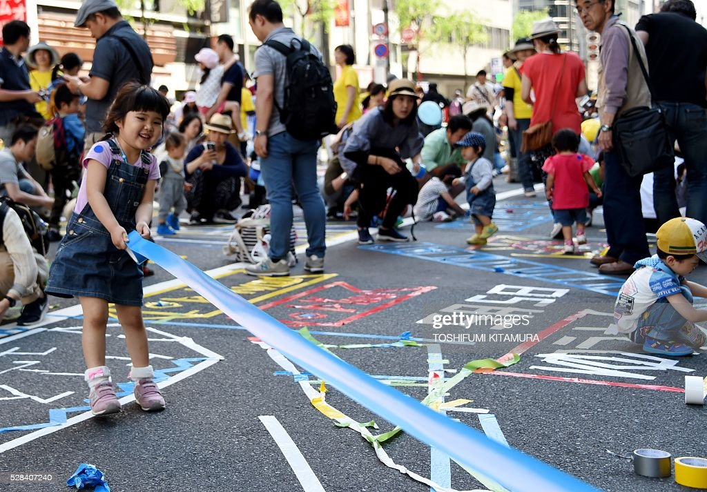 Children make pictures with colourful tapes on a street during the Ginza 'Yanagi' festival at the Ginza shopping district in Tokyo on May 5, 2016. / AFP / TOSHIFUMI