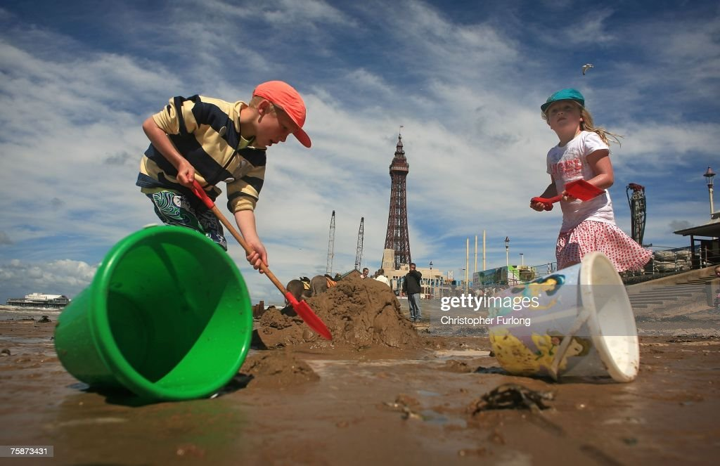 Children make sand castlesl as holiday makers enjoy the warm but windy weather on July 30, 2007, Blackpool, England. After the recent floods and unseasonal weather Britons are heading for the seaside for a traditonal day by the sea. Blackpool resort has always been one of the top British seaside holiday destinations from its Victorian origins and heyday in the 1950s to it's attempts at reinvention today with plans to turn it into Britain's equivalent of Las Vegas.