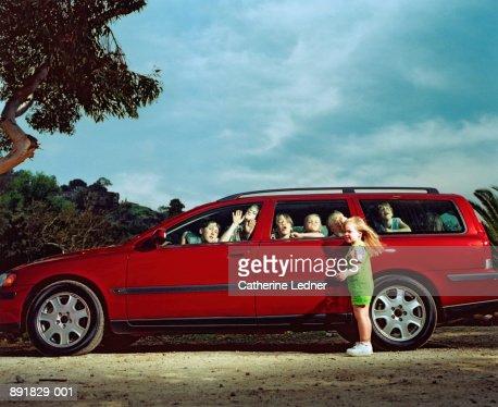 Children (5-10) making faces inside car windows, girl locked outside
