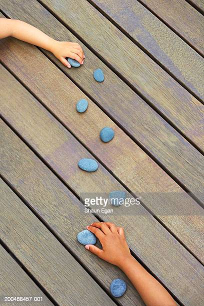 Children (3-5) making pattern with stones on floor