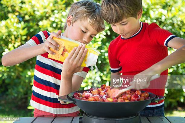 Children making plum jam step by step