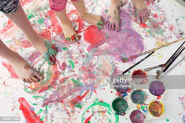 Children messy painting with feet