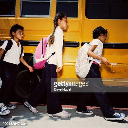 Children (5-7) near school bus, side view : Stock Photo