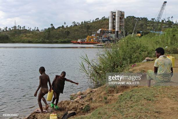 Children of fishermen stand on the bank of Lake Kivu in the Rwandan border town of Rubavu on May 2 2014 Beneath the calm waters of Lake Kivu lie vast...