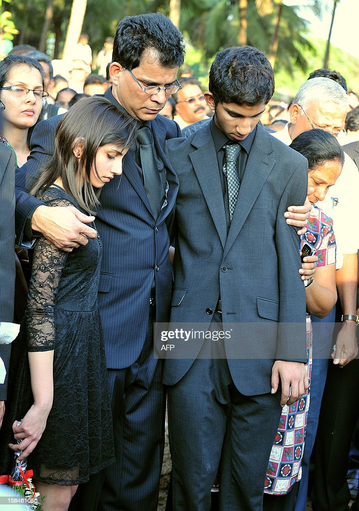 Children of late nurse Jacintha Saldanha, daughter Lisha Saldanha (L) and son Junal Saldanha (R) are consoled by their father Benedict Barbosa during their mother's funeral at The Shirve Church cemetary near Mangalore on December 17, 2012. About 2,000 mourners have packed a Catholic church in southwest India for the funeral of the nurse who was found hanged after taking a hoax call to the hospital treating Prince William's wife. Indian-born Jacintha Saldanha, 46, apparently committed suicide after answering the telephone call from Australian radio DJs to the hospital where the pregnant Duchess of Cambridge was admitted with acute morning sickness.AFP PHOTO/Manjunath KIRAN