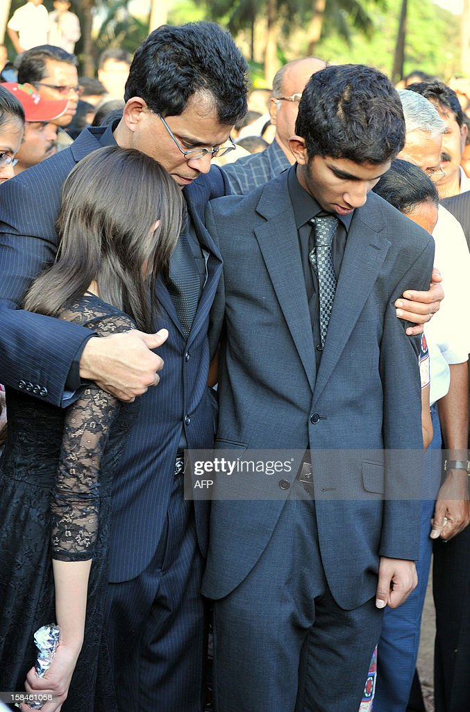 Children of late nurse Jacintha Saldanha, daughter Lisha Saldanha (L) and son Junal Saldanha (R) are consoled by their father Benedict Barbosa (C) during their mother's funeral at The Shirve Church cemetary near Mangalore on December 17, 2012. About 2,000 mourners have packed a Catholic church in southwest India for the funeral of the nurse who was found hanged after taking a hoax call to the hospital treating Prince William's wife. Indian-born Jacintha Saldanha, 46, apparently committed suicide after answering the telephone call from Australian radio DJs to the hospital where the pregnant Duchess of Cambridge was admitted with acute morning sickness.AFP PHOTO/Manjunath KIRAN