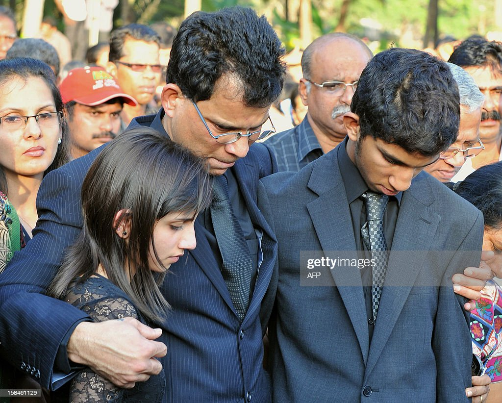 Children of late nurse Jacintha Saldanha, daughter Lisha Saldanha (L) and son Junal Saldanha (R) are consoled by their father Benedict Barbosa (C) during their mother's funeral at The Shirve Church cemetary near Mangalore on December 17, 2012. About 2,000 mourners have packed a Catholic church in southwest India for the funeral of the nurse who was found hanged after taking a hoax call to the hospital treating Prince William's wife. Indian-born Jacintha Saldanha, 46, apparently committed suicide after answering the telephone call from Australian radio DJs to the hospital where the pregnant Duchess of Cambridge was admitted with acute morning sickness. AFP PHOTO/Manjunath KIRAN