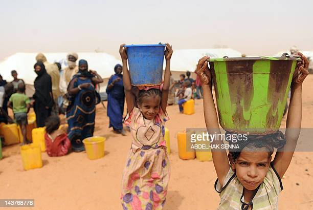 Children of Malian refugees carry buckets full of water at the Mbere refugee camp on May 3 near Bassiknou southern Mauritania 60 km from the border...