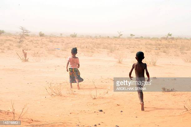 Children of Malian refugees walk bare feet on the burning sand as temperatures are close to 40° Celsius at the Mbere refugee camp on May 3 near...