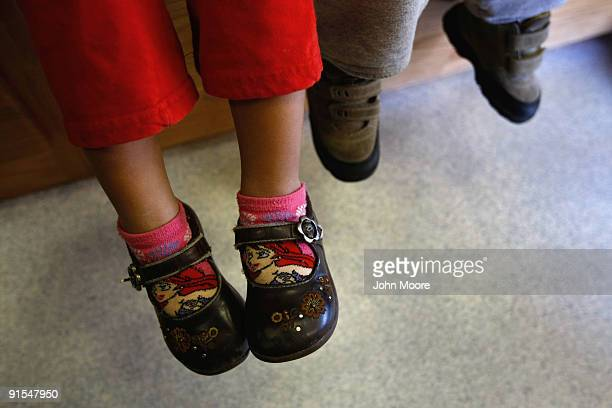 Children of Mexican immigrants wait to receive a free health checkup inside a mobile clinic at the Mexican Consulate on October 7 2009 in Denver...