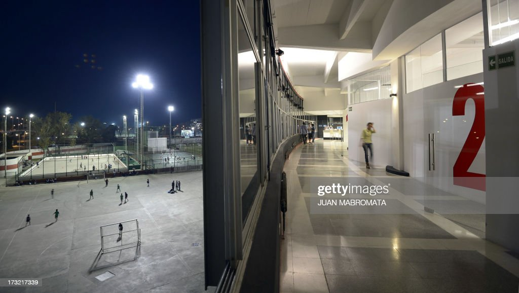Children of River Plate's football school (L) are seen training from a window of the Monumental stadium in Buenos Aires on June 13, 2013 where is located the Instituto Universitario River Plate (River Plate's University Institute), the first sports institution that completes the educational cycle, from kindergarten to the university.