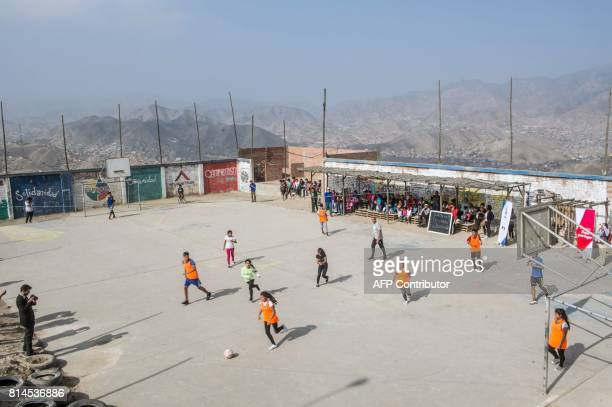 Children of San Pablo Mirador community Chancay district in the outskirts of Lima play a football match with former French world football champion...