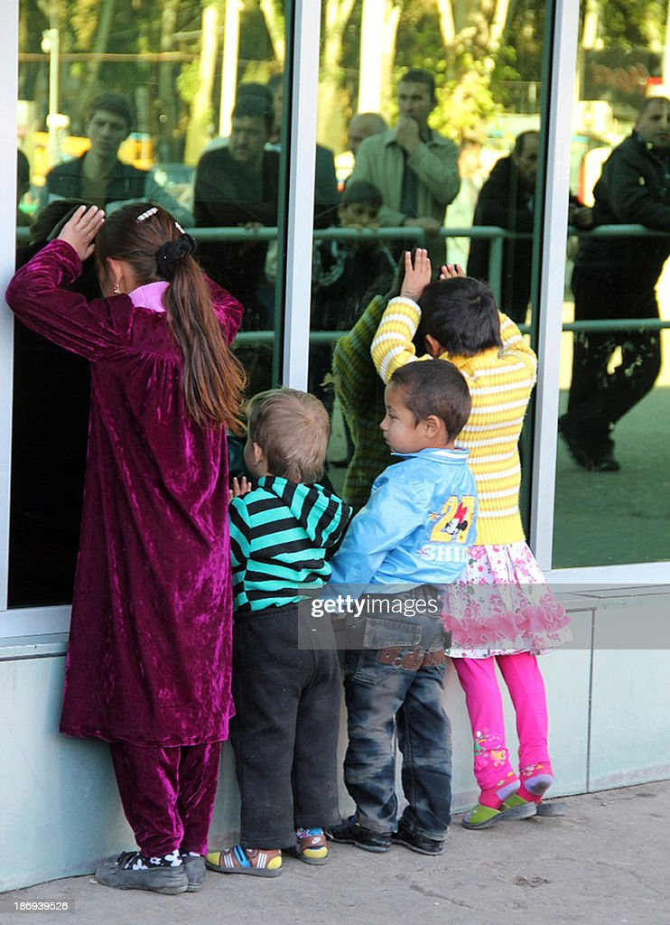 Children of Tajik migrant workers in Russia wait for their arrival at the airport in the Tajikistan's capital Dushanbe, on November 2, 2013. Thousands of Tajik families are torn apart by the ex-Soviet state's enduring economic crisis, which has forced an estimated one million men of working age to seek work abroad, mainly in Russia.