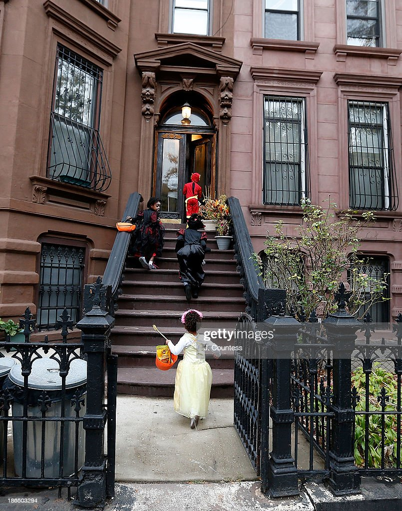 Children of the Jefferson Village Block Association collect candy as they 'Trick or Treat' at local residences in BedfordÐStuyvesant, Brooklyn on October 31, 2013 in New York City.