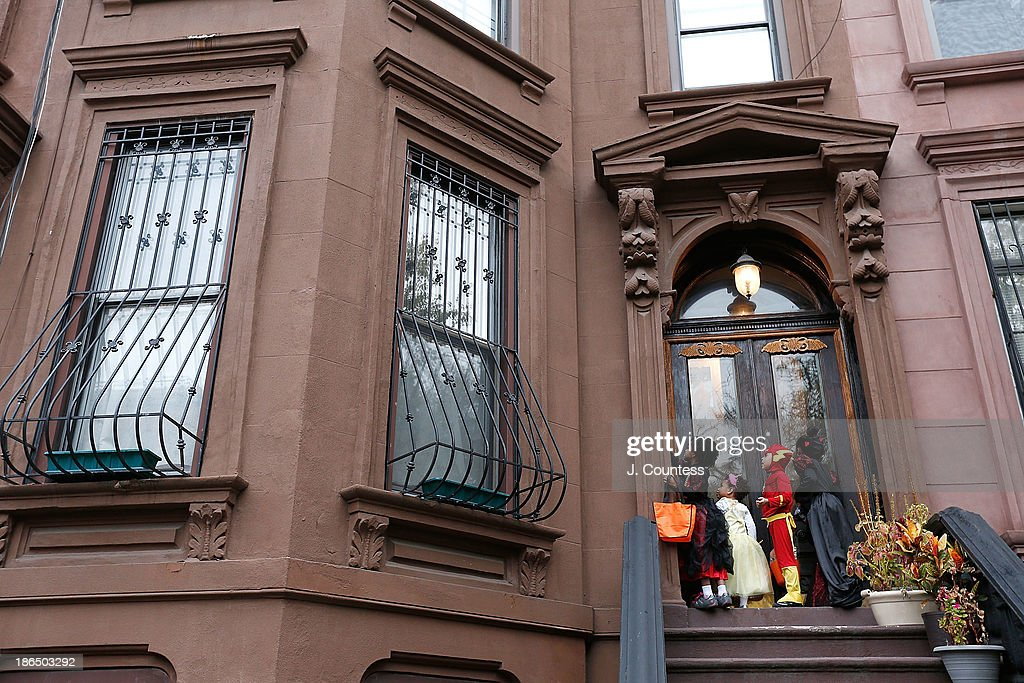 Children of the Jefferson Village Block Association ring the doorbell of a local residence as they 'Trick or Treat' at local residences in BedfordÐStuyvesant, Brooklyn on October 31, 2013 in New York City.