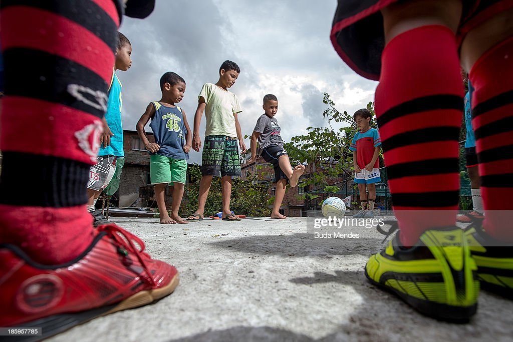 Children of Vila Nova Project, play football on the rooftops in the Morro dos Macacos area on October 26, 2013 in Rio de Janeiro, Brazil. The Project Vila Nova was idealized by Alex Sandro and has so far run for 2 years, catering to children and young residents of the Morro dos Macacos area.