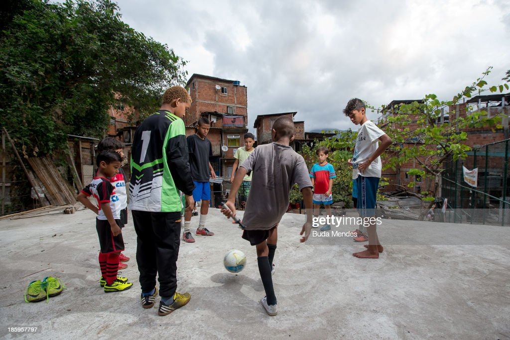 Children of Vila Nova Project, plays football on the rooftops in the Morro dos Macacos area on October 26, 2013 in Rio de Janeiro, Brazil. The Project Vila Nova was idealized by Alex Sandro and has so far run for 2 years, catering to children and young residents of the Morro dos Macacos area.