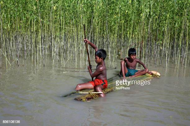 children on a raft approach a boat in Guthail Jamalpur Bangladesh on 19 August 2017