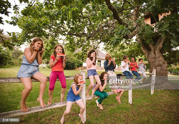 Children on a wooden fence eating watermelon on summer day