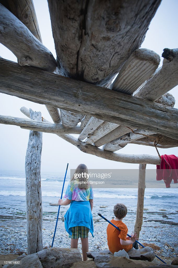 children on beach with driftwood shack : Stock Photo