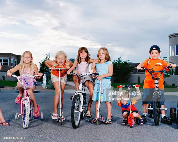 Children (3-11) on bicycles and scooters in street, portrait