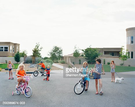 Children (3-11) on bicycles and scooters playing in cul-de-sac