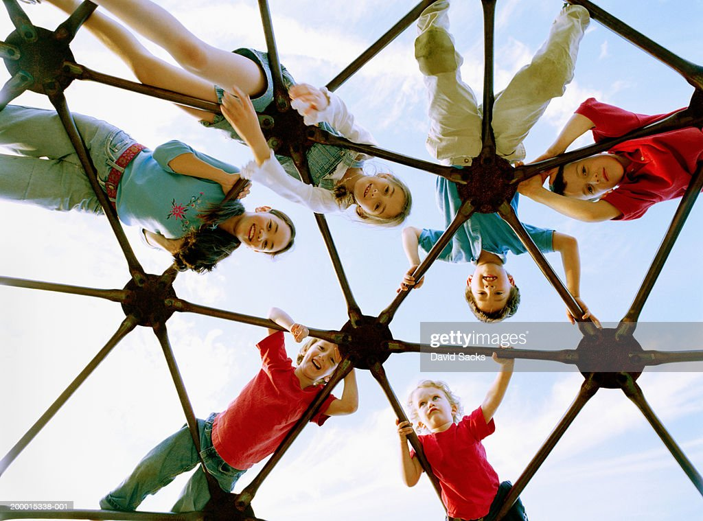 Children (3-13) on climbing dome, portrait, low angle view