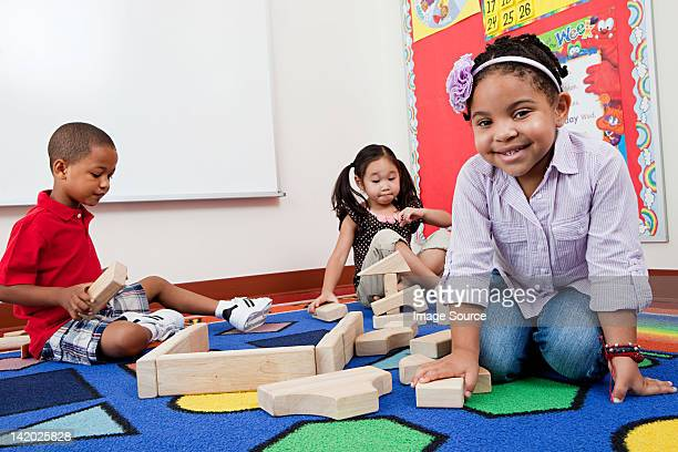 Children on floor with building blocks
