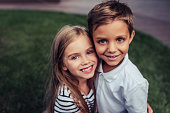 Couple of charming childs having fun outdoors. Portrait of beautiful girl and boy are hugging, smiling and looking at the camera. Little brother and sister in park on a green grass.