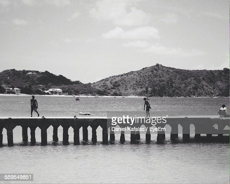 Children On Pier At Sea By Mountains Against Sky
