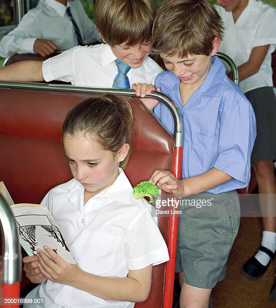 Children (6-10) on school bus, boy placing toy frog on girl's shoulder