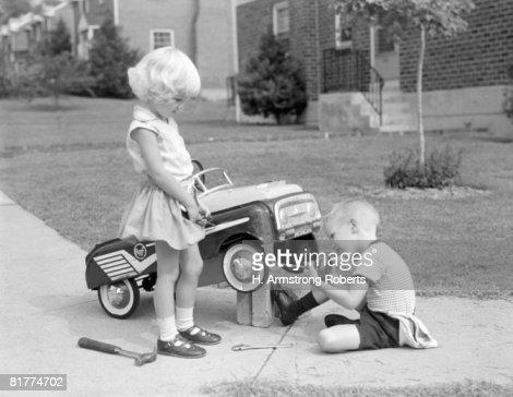 Children on suburban sidewalk, boy playing as mechanic, oiling toy pedal car.
