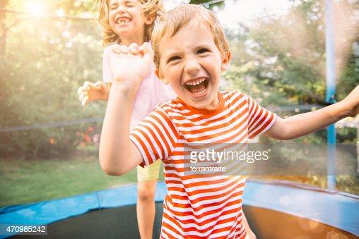Bambini su vacanze estive saltando sul trampolino per
