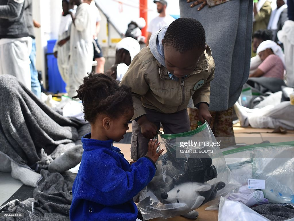 Children pack their cuddly toys in plastic bags prior to leave rescue ship 'Aquarius' as more than 380 migrants arrive in the port of Cagliari, Sardinia, on May 26, 2016, two days after being rescued near the Libyan coasts. The Aquarius is a former North Atlantic fisheries protection ship now used by humanitarians SOS Mediterranee and Medecins Sans Frontieres (Doctors without Borders) which patrols to rescue migrants and refugees trying to reach Europe crossing the Mediterranean sea aboard rubber boats or old fishing boat. / AFP / GABRIEL