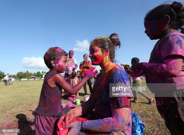 Children paint a woman with colorful abeer powder to commemorate Holi which celebrates the arrival of the season of Spring as part of the annual...