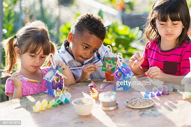 Children painting bird houses