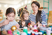 Portrait of two cute little girls making Christmas decorations in art and craft class with female teacher helping them