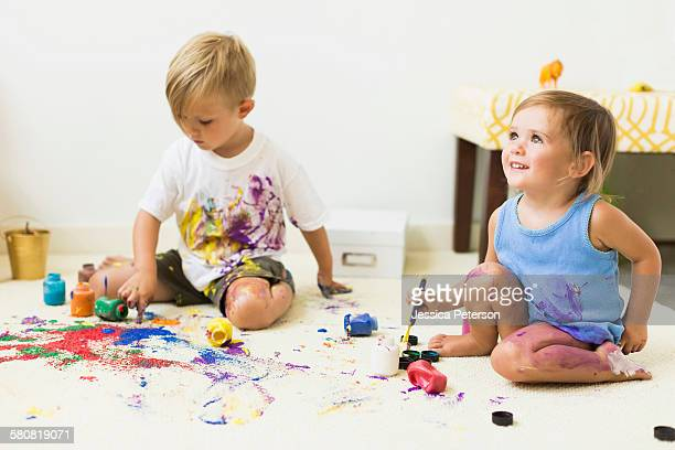 Children (2-3) painting on carpet