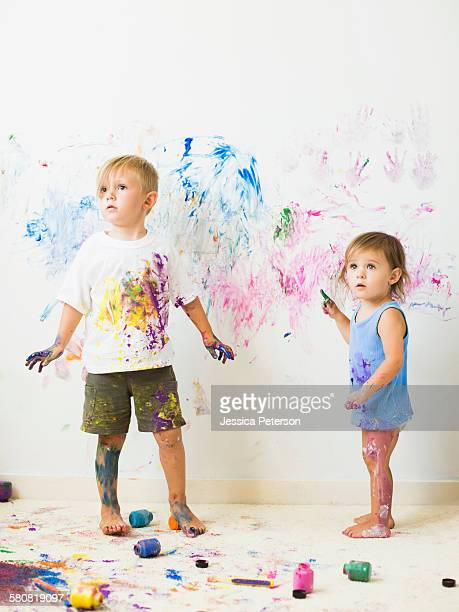 Children (2-3) painting on wall