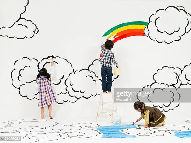 Children painting rainbow and cloud on the wall