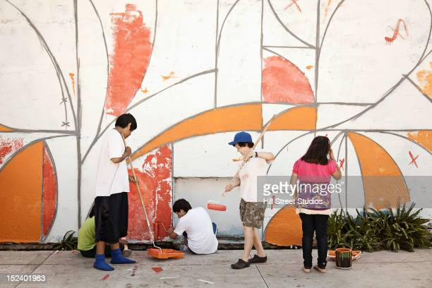 Children painting wall together