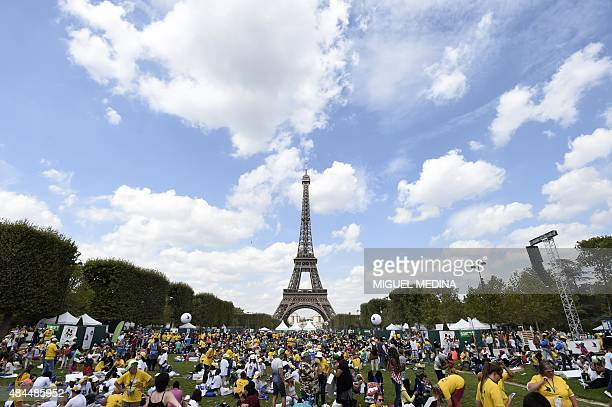 Children participate in activities in front of the Eiffel Tower in Paris on August 19 2015 during the 'Journee mondiale des oublies des vacances'...
