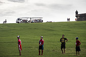 Children pause during a baseball game as tourists travel in a people mover near the Castillo San Felipe del Morro in San Juan Puerto Rico on Sunday...
