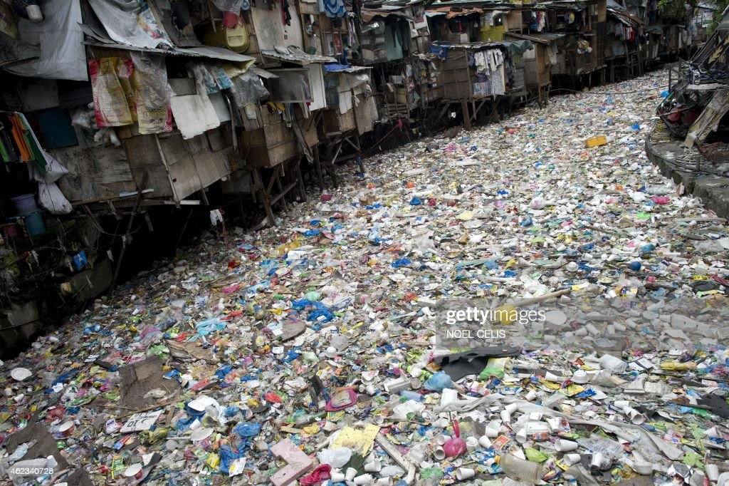 Children peek at a window beside a river filled with garbage in Manila on January 27, 2015.